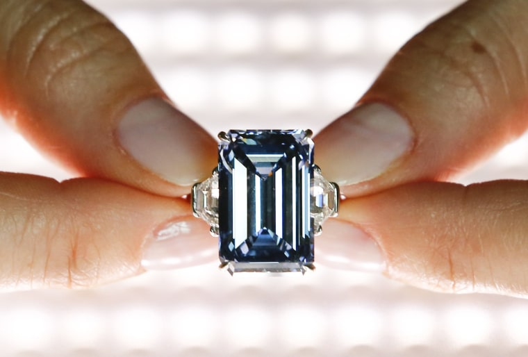 Image: A Christie's employee poses with the 14.62 carats Oppenheimer Blue diamond during a preview in Geneva