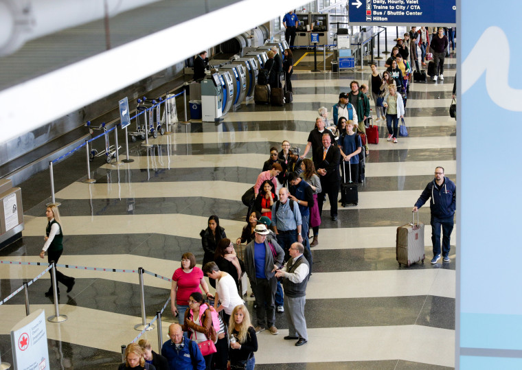 A long line of travelers wait for the TSA security check point at O'Hare International airport, in Chicago on May 16, 2016. Already faced with lines that snake through terminals out to the curb, fliers are bracing for long waits at security in the busy months of July and August. At O'Hare, temporary contractors hired by American Airlines began helping with non-essential screening functions like moving bins and managing the lines of waiting travelers to alleviate lines.