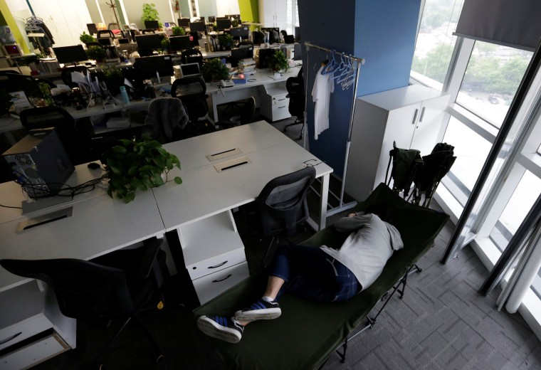 Image: The Wider Image: Working, eating and sleeping at the office