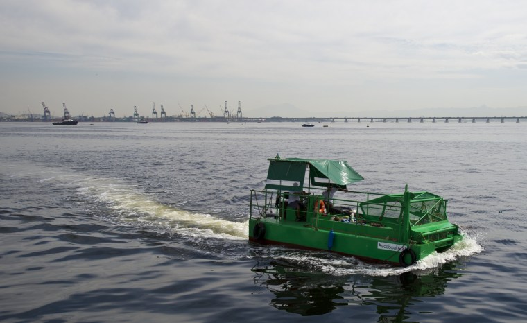 "The cleaning vessel ""Ecoboat"" sails across the polluted waters of Guanabara Bay in Rio de Janeiro, Brazil"