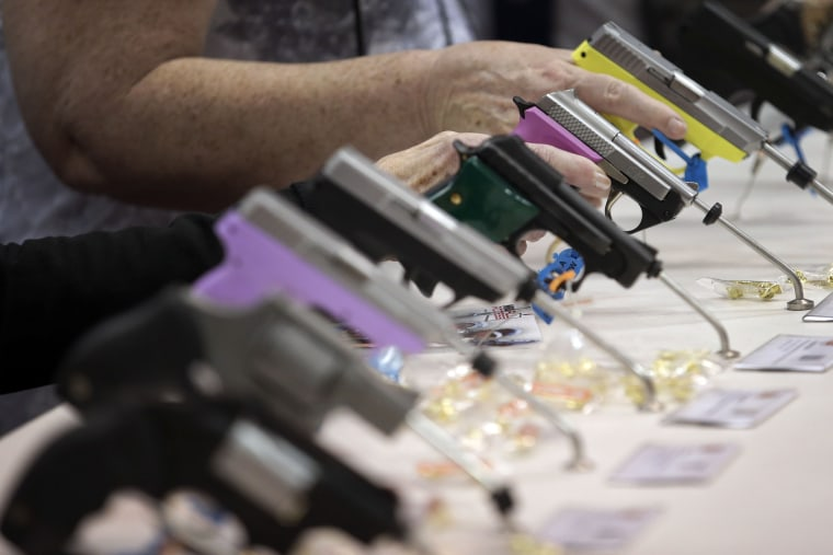 Attendees look over a pistol display at the National Rifle Association's annual convention in Friday, April 25, 2014 in Indianapolis.