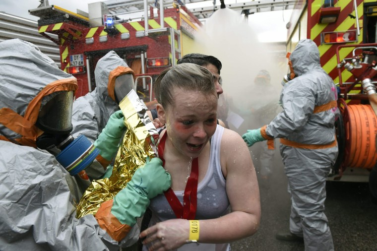 """Image: Firefighters help """"victims"""" during mock chemical attack exercise on April 4, 2016"""