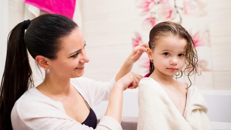 Mother brushing child hair