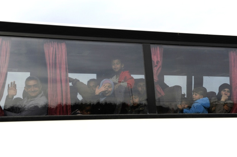 Image: Refugees and migrants are transferred on a bus to government camps, during a police operation to evacuate a makeshift camp near the village of Idomeni