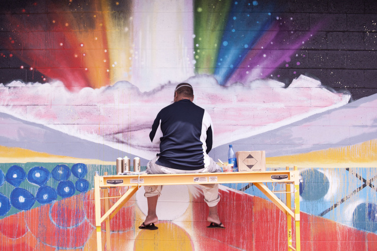 """John """"Prime"""" Hina -- one of the artists featured in """"Mele Murals"""" -- painting a community mural in Waimea, Hawaii."""