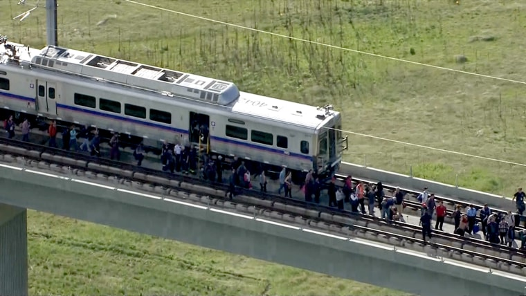 Eighty passengers were stuck 50 feet above the ground after the rail line to Denver International Airport got stuck on an overpass above Pena Boulevard Tuesday afternoon.