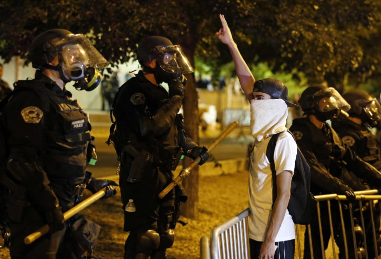 Image: Riot police face off with a protester in Albuquerque