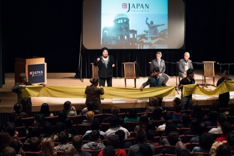 Thurlow speaking at a Japan Society event. The yellow banner contains 331 names of girls from Thurlow's school who died on Aug. 6, 1945.