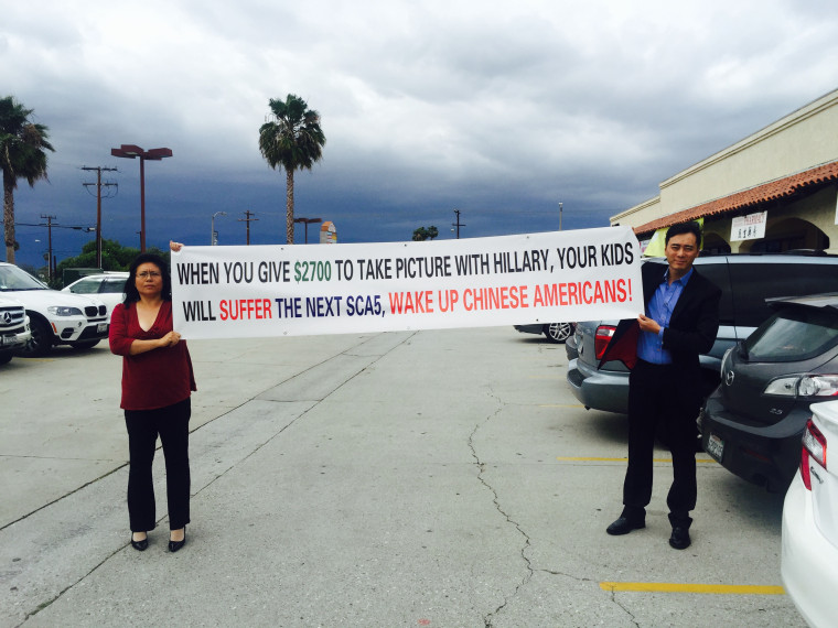 Wang, left, displaying one of Chinese Americans for Trump's signs.