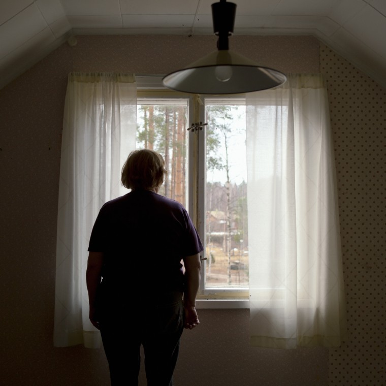 Finland, Senior woman sitting on bed, looking through window