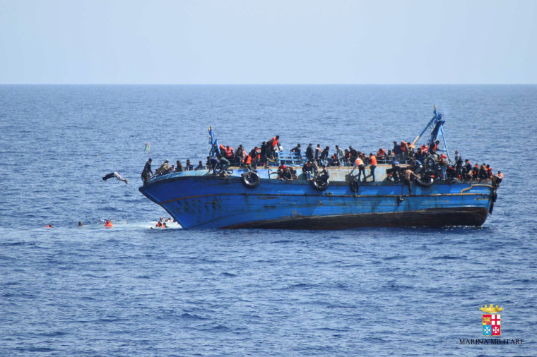 """Image: Migrants are seen on a capsizing boat before a rescue operation by Italian navy ships """"Bettica"""" and """"Bergamini"""" (unseen) off the coast of Libya"""