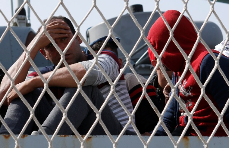 """Image: Migrants are seen before to disembark from Italian navy ships """"Bettica"""" in the Sicilian harbour of Porto Empedocle"""