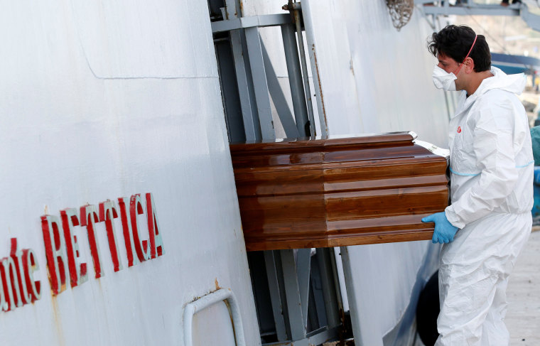 """Image: A coffin containing a migrant is removed from Italian navy ships """"Bettica"""" in the Sicilian harbour of Porto Empedocle"""