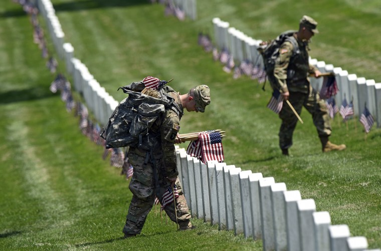 Image: Members of the Old Guard place flags in front of every headstone at Arlington National Cemetery