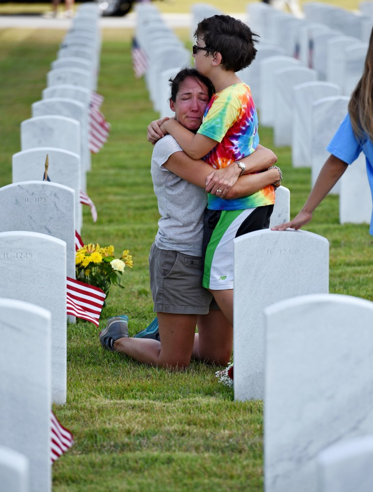 Image: A mother and son hug and the grave marker of her father