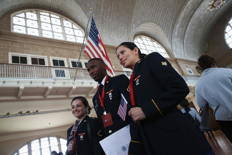 Image: Service members pose for photos after receiving their U.S. citizenship at a naturalization ceremony