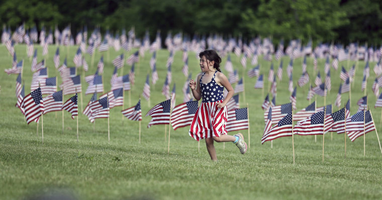 Image: A young girl wears a flag-design dress as she runs near thousands of flags