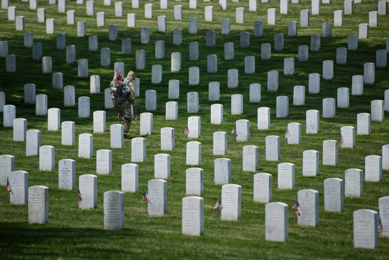 Image: Members of the U.S. Army place American flags at graves at Arlington National Cemetery