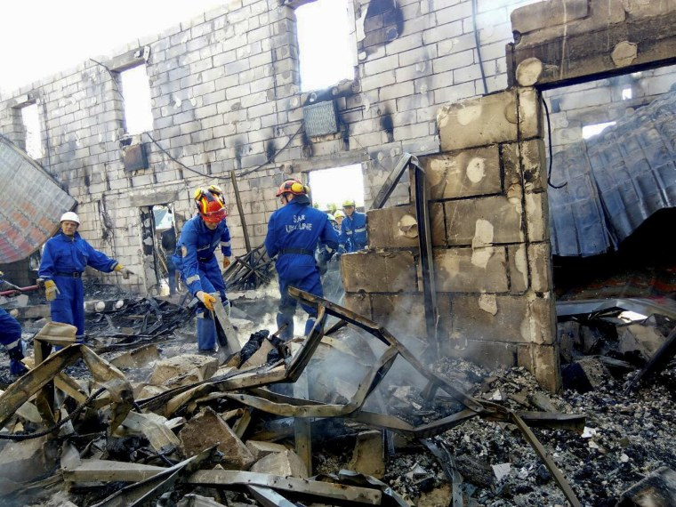 Image: Rescuers inspect the debris of a residential house after a fire broke out, in the village of Litochky