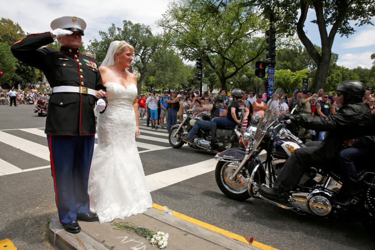 Image: Tim Chambers stands with his new bride Lorraine Heist as riders pass by during the Rolling Thunder motorcycle rally in Washington