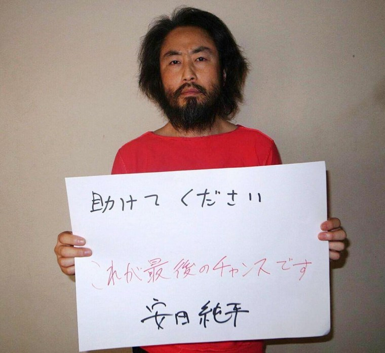 Image: The undated picture, released by Japan's Jiji Press news agency, purports to show Jumpei Yasuda holding a handwritten message.