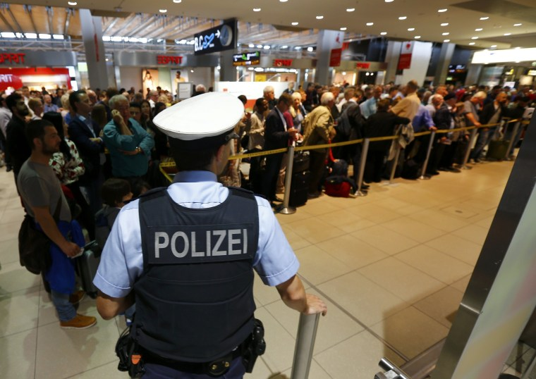 Image: A police officer stands in front of passengers lining-up at the entrance to Cologne airport following security alert