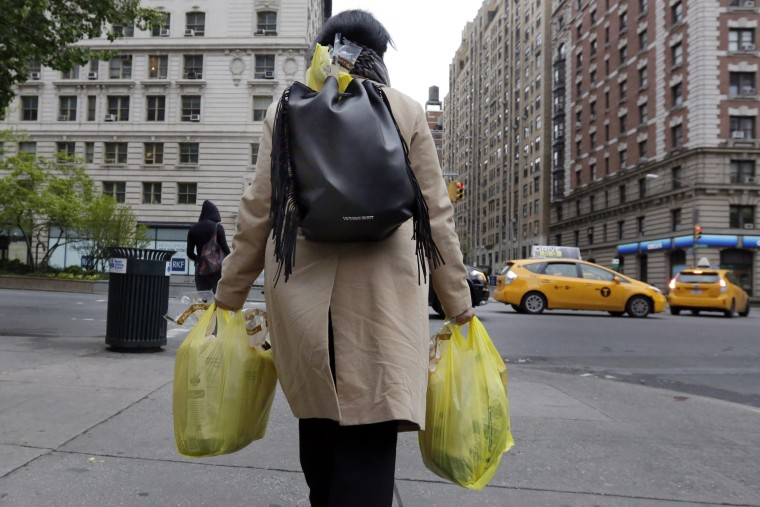 A woman carries her purchase in plastic bags from a Gristedes supermarket on New York's Upper West Side