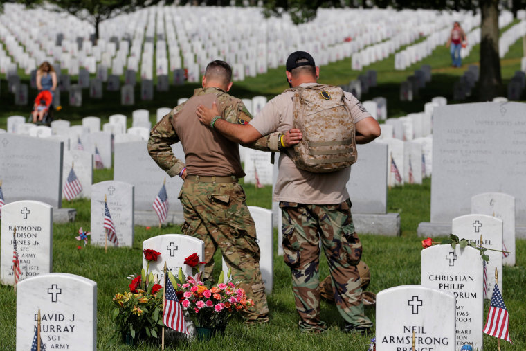 U.S. Army soldiers Rick Kolberg and Jesus Gallegos embrace as they visit the graves of Raymond Jones and Peter Enos on Memorial Day at Arlington National Cemetery in Washington, May 30, 2016.
