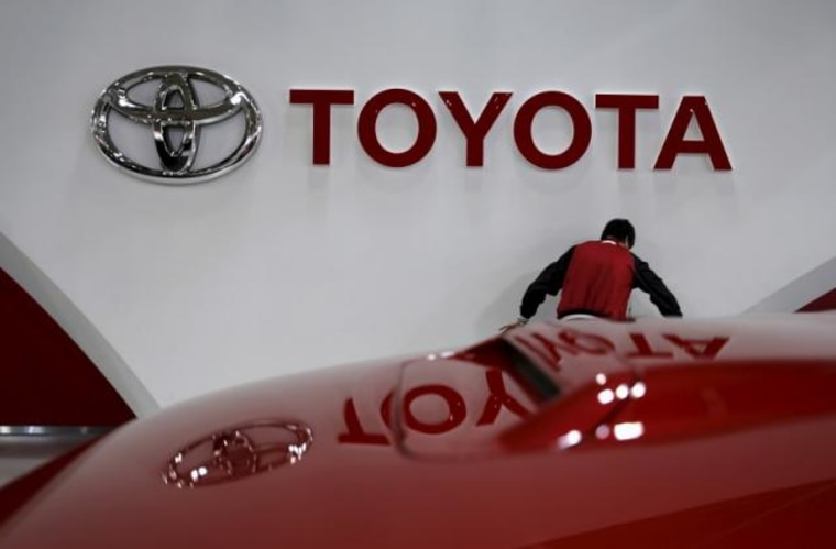 An employee works under a Toyota Motor Corp logo at the company's showroom in Tokyo
