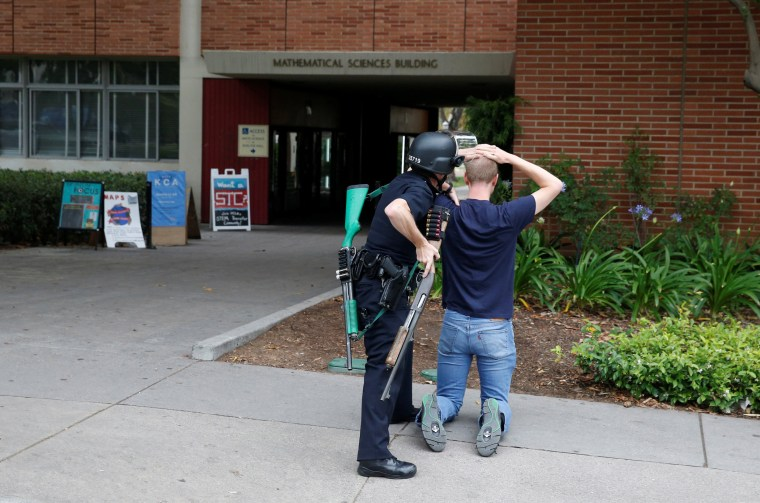 Image: A police officer searches a student at the University of California, Los Angeles campus after it was placed on lockdown following reports of a shooter on the campus in Los Angeles