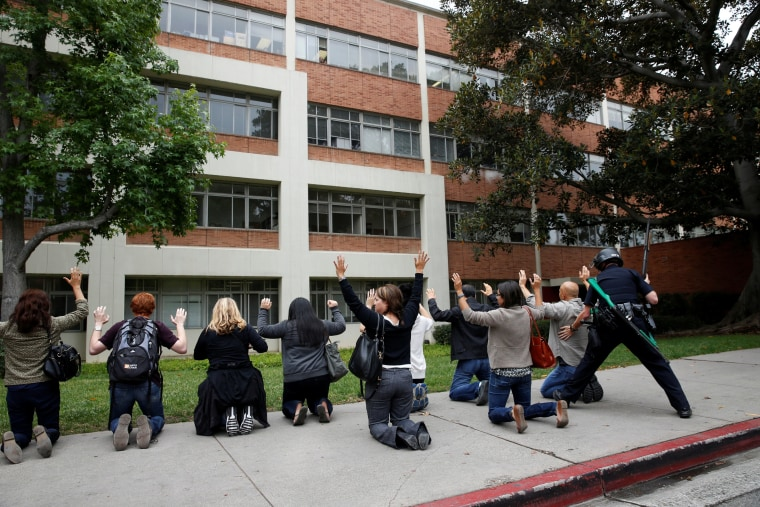 Image: A police officer conducts a search on people at the UCLA campus after it was placed on lockdown following reports of a shooter that left 2 people dead in Los Angeles, California