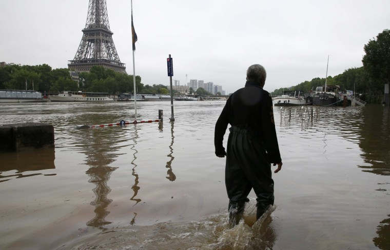 Image: A man walks on a flooded road near his houseboat moored near the Eiffel towel during flooding on the banks of the Seine River in Paris