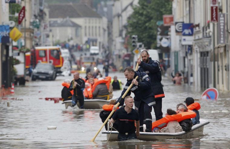 Image: French firefighters on small boats evacuate residents from a flooded area after heavy rainfall in Nemours