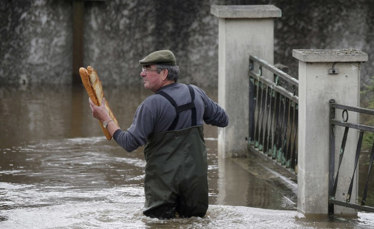 Image: A resident brings French baguettes to his mother's flooded house after heavy rain falls in Chalette-sur-Loing Montargis