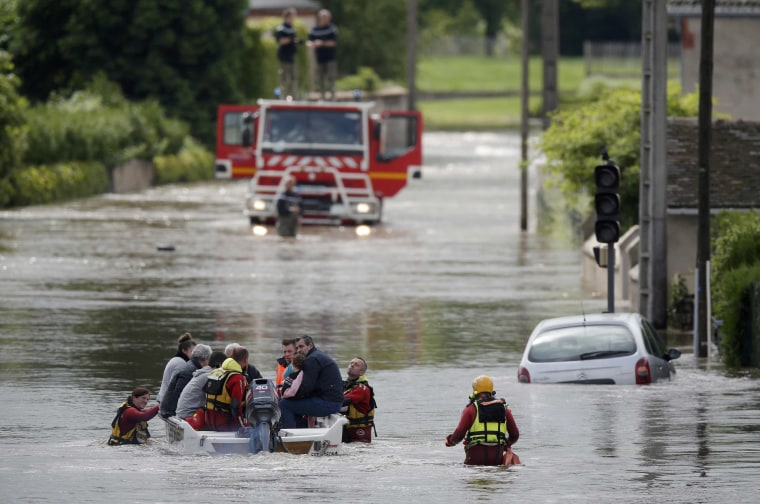 Image: French firefighters on a small boat evacuate residents from a flooded area after heavy rain falls near Montargis