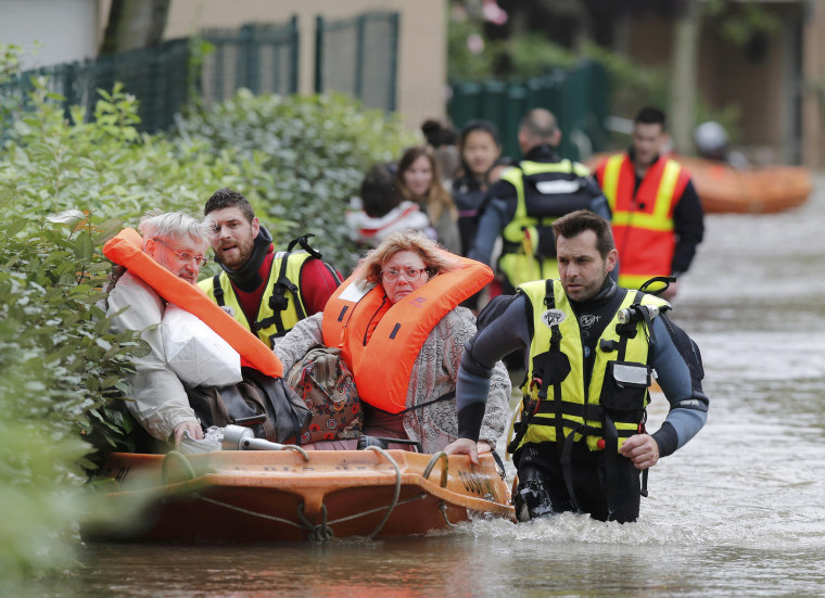 Image: French firefighters on a small boat evacuate residents from a flooded area after heavy rain in Longjumeau