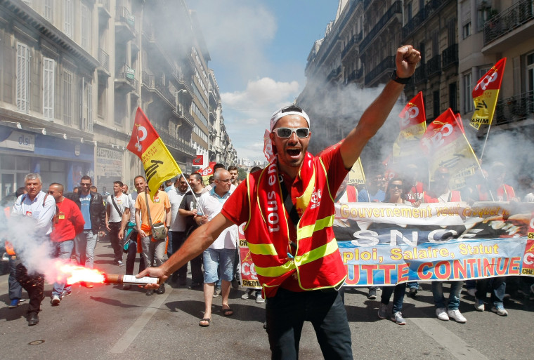 Image: A worker burns a flare during a demonstration in Marseille, Thursday, another day of strikes and protests against government labor reforms.