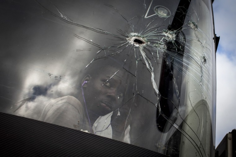 Image: A passenger looks through a bus windshield with bullet holes