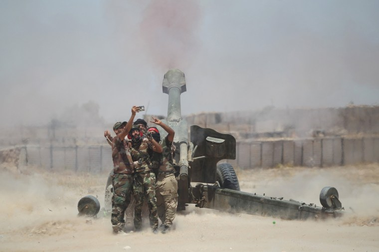 Image: Shi'ite fighters take a selfie while firing artillery towards Islamic State militants near Falluja
