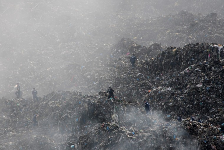 Image: Rescue workers investigate a trash dump in Ukraine