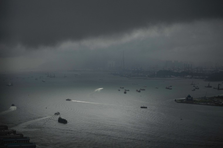 Image: Passenger ferries and other maritime vessels are seen in a spot of light from a break in storm clouds over Victoria Harbour