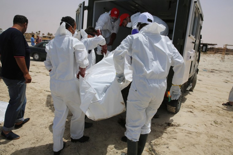 Image: Libyan officials remove a body from a beach