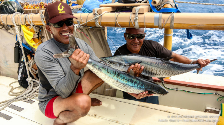 Nainoa Thompson, left, president of the Polynesian Voyaging Society and master navigator, on board Hokulea with a fish caught from the ocean.