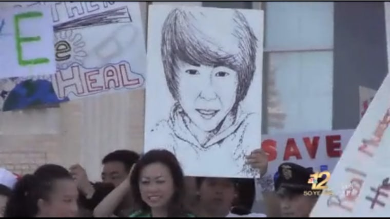 Dylan Yang supporters hold signs during a peace march.