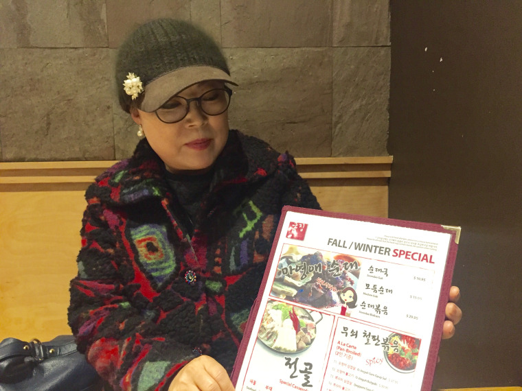 Youngae Ma with the menu featuring her North Korean-style sausages.