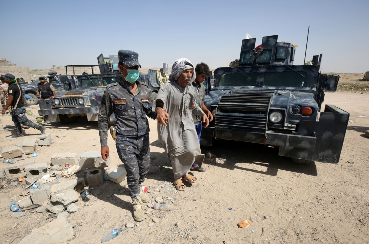 Image: Members of the Iraqi government forces help a man who fled the violence