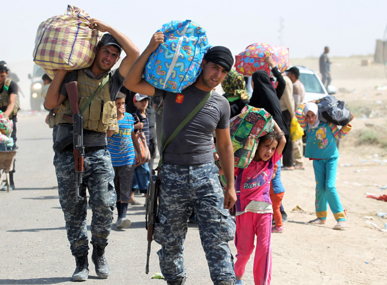 Image: Members of the Iraqi government forces help people who fled the violence