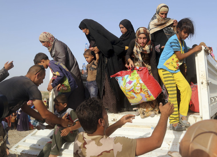 Image: Iraqi soldiers help families from a vehicle outside an Iraqi army military Camp near Fallujah