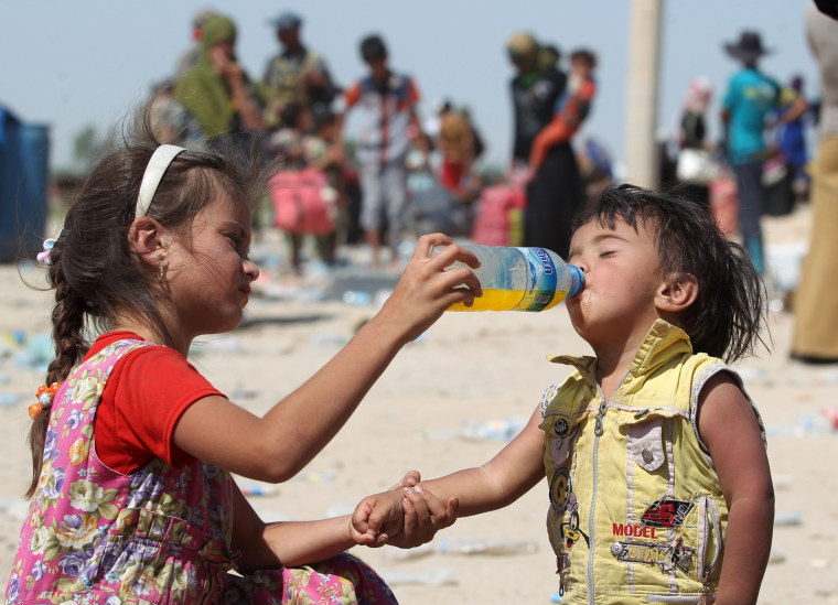Image: An Iraqi girl helps a young boy drink as they receive food and aid at a military point