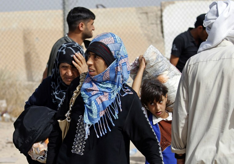 Image: Displaced Iraqi families arrive to an Iraqi army camp after fleeing their homes